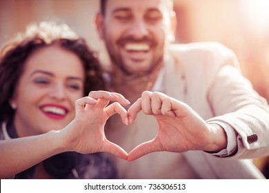 Close up of couple making heart shape with hands.