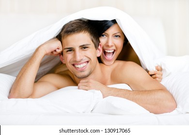 Close up of couple playing in bedroom. Covered with blanket woman lying on the back of the man