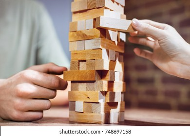 Close up couple playing jenga indoor on table