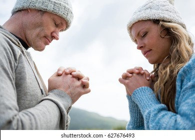 Close up of couple praying with hands clasped on beach
