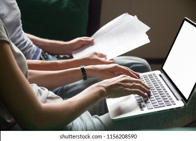 Close up of couple searching online information about legal document details with laptop, family studying important contract terms and conditions typing filling internet application form on website