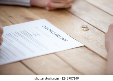 Close up of couple sign divorce decree with marriage rings lying on table, family separated putting signature on legal documents, unhappy spouse finalize relationships, breaking up at lawyers office