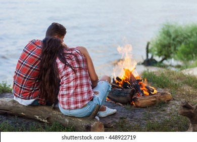 close up of couple sitting near fire on beach