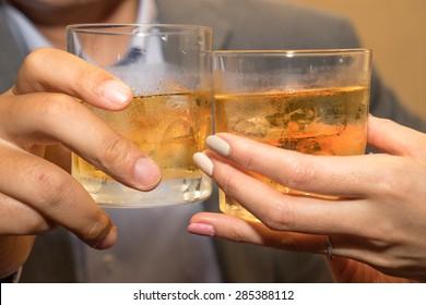 Close up of couple toasting whiskey glasses