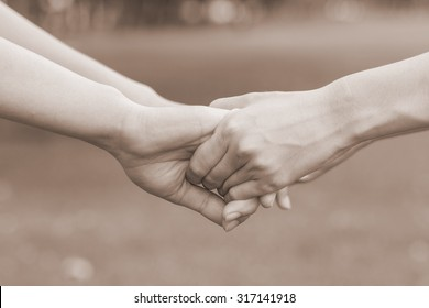 close up couple women hands reaching hold and touch together for forgiving and cheer up for help and stronger life concept in image sepia vintage tone color.
