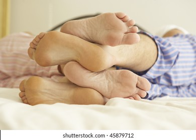 Close Up Of Couple's Feet Relaxing On Bed At Home