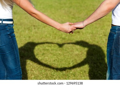 Close up of couples hands together with shadow of heart sign.