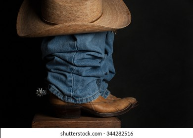 A close up of a cowboy boot, spur, and hat / Jeans and Cowboy Hat / A close up of a cowboy boot, spur, and hat against a dark background