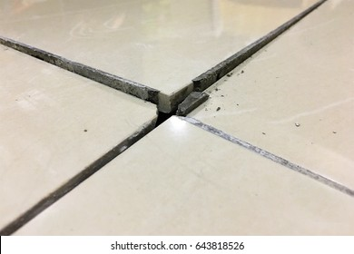 Close up of a cracked ceramic tiles on a residential house floor surface due to improper construction material.