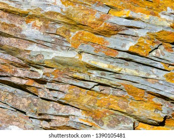 Close up of cracked and layered grey Welsh slate with patches of orange and brown lichen
