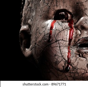 Close up of a Cracked Scary Doll Crying Blood in Horror