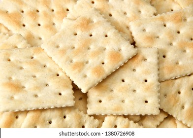 Close up of crackers filling entire image, known as saltines, soda and soup crackers.