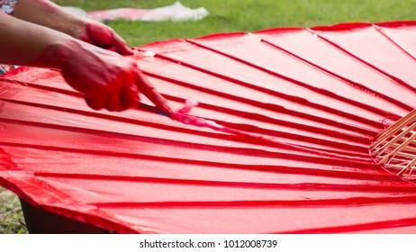 Close up craftsman hand painting red umbella