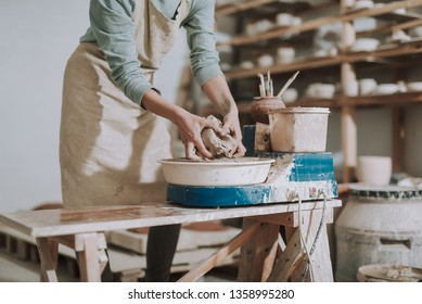 Close up of craftswoman kneading and shaping clay on pottery wheel