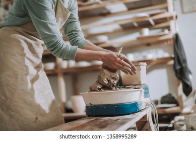 Close up of craftswoman removing clay from her hands. She standing near pottery wheel