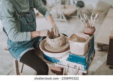 Close up of craftswoman sitting on bench and making clay pot in pottery workshop