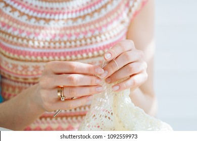 Close up of craftswoman's hands knitting dress with crochet. Female working with tender lace. Business handmade crochet relaxation concept.