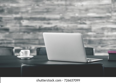 Close up of creative designer desktop with blank laptop monitor, book and coffee cup. Blurry wooden wall in the background. Mock up