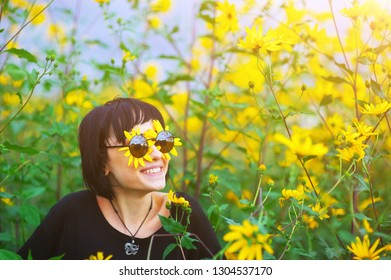 Close up creative portrait of a beautiful young smiling joyful brunette girl with yellow flower petals under sunglasses on background of a field of sunflowers. Sunflare, sunbeams, glow sun. Backlit.