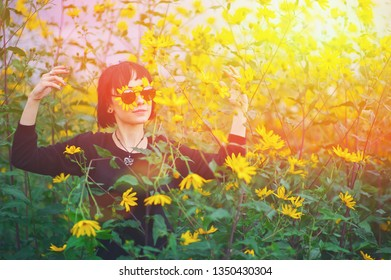 Close up creative portrait of a beautiful young smiling happy brunette girl with yellow flower petals under sunglasses on background of a field of sunflowers. Sunflare, sunbeams, glow sun. Summer.