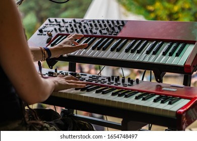 A close up creative view with soft focus on the hands of a person playing two tier synthesizer keyboard on stage at earth festival, copy space to right