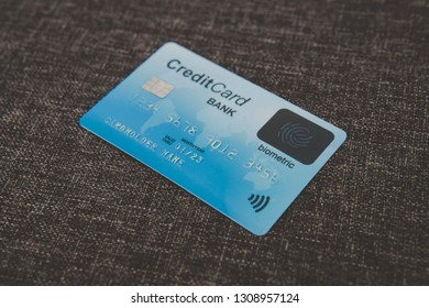 Close up of credit biometric card belonging to abstract cardholder lying on coarse fabric. E-shopping using advantages of fingerprint scanning. Simplicity and security of biometrics in banking. Chip