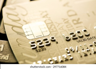 Close up of credit card with chip and numbers, golden theme