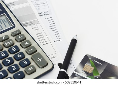 close up of a credit cards with credit card statements, pen and calculator on white background, copy space