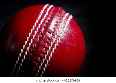 Close up of a cricket ball seam with black background