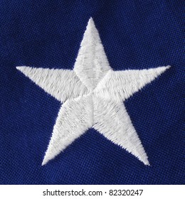 Close of a crisp white embroidered star on a US Veteran's flag