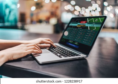 Close up crooped shot of female hands using laptop. Girl sitting in loft coffee shop and making bets online on sport bookmaker's webcite.
