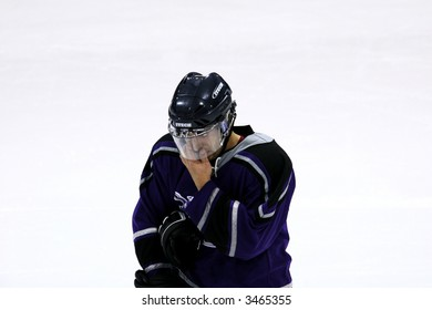 Close crop of a hockey player with a visor on during a hockey game.  Player is in early 20s.
