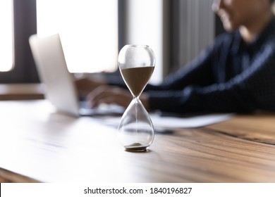 Close up crop of hourglass on wooden home office table count measure time. Female worker employee work on laptop on background, make plan or meet deadline. Time management, efficiency concept.