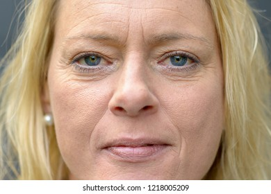 Close up cropped face portrait of an attractive middle-aged blond woman with blue eyes wearing subtle make-up