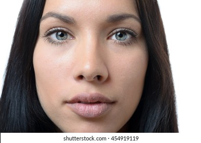 Close up cropped frontal view of the face of a serious young woman with grey eyes and long dark hair staring at the camera, on white