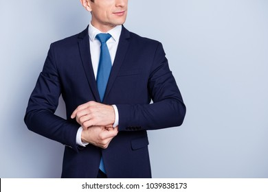 Close up cropped half face portrait of attractive, corporate, perfect, stylish man in formal wear, blue suit, fixing buttons on a cuff of white shirt, standing over gray background
