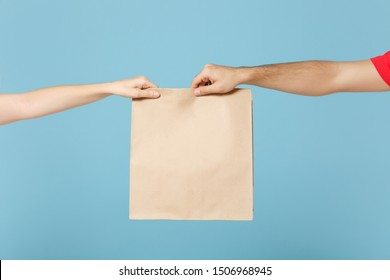 Close up cropped hands hold brown clear empty blank craft paper bag food for takeaway isolated on blue background. Packaging template mock up. Delivery service concept. Copy space. Advertising area
