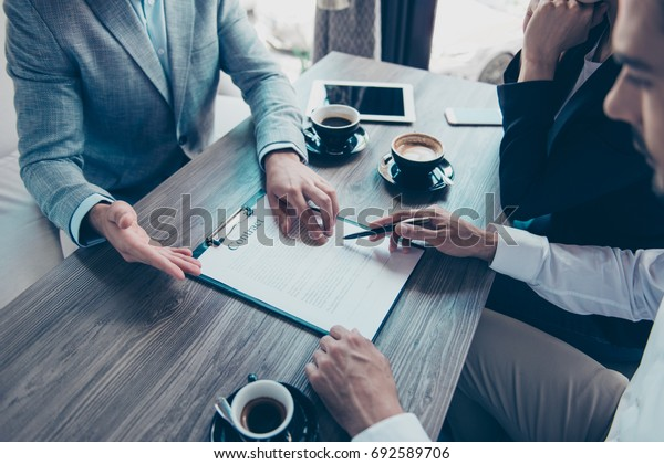 Close up cropped high angle view of young people making a deal with lawyer about their business in cafe with cups of coffee. Men is going to sign contract to complete the deal