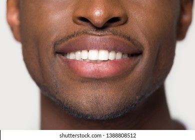 Close up cropped image african attractive young man face part having ultra snow white smile healthy straight teeth isolated on grey background wall. Dental oral health care whitening dentistry concept