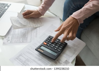 Close up cropped image coffee table full with papers invoices cheque bills, female hands holding receipt calculating company expenses results of incomes, bookkeeper accountant doing paperwork concept