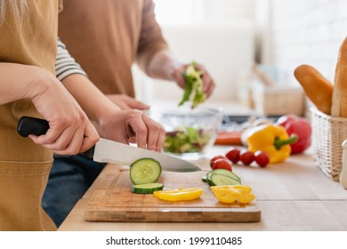 Close up cropped image of cutting board and couple cutting vegetables in the kitchen together, preparing food meal at home. Vegetarian healthy food - Shutterstock ID 1999110485