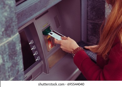 Close up  cropped image of hand pulling in debit card at an ATM. Hand of woman uses credit card to withdraw at Bank terminal. Modern style. ATM cash terminal with display