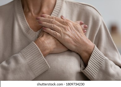 Close up cropped image hopeful grateful mature senior woman keeping hands on chest, mindful middle aged female thanking god and faith, feeling love, gratitude, appreciation, making wish