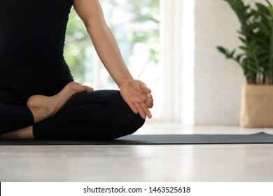 Close up cropped image view womans legs in black sporty pants sitting in lotus pose fingers folded I mudra gesture on mat indoors, female do meditation breathing feels no stress anxiety relief concept