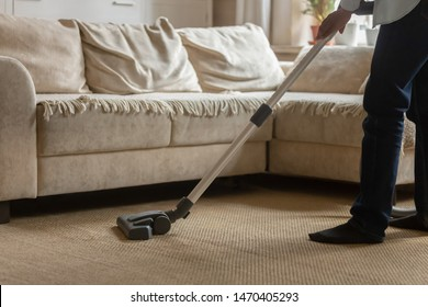 Close up cropped image young african american guy using vacuum cleaner, cleaning whitish carpet, removing dust in modern living room, daywork routine, housekeeping, home routine concept.