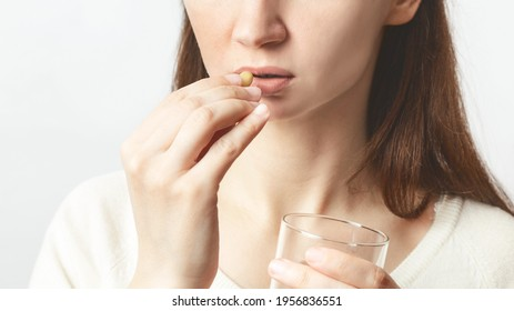 Close up cropped image of young caucasian girl holding pill and glass of fresh water, taking medicine for headache, abdominal pain or taking vitamins, sedatives, health care concept