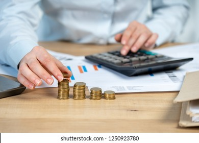 Close up cropped investor or sale manager lady in her formal wear shirt she put money in pile sit behind table in bright loft interior workstation count tax on invoice focus on hand with coins