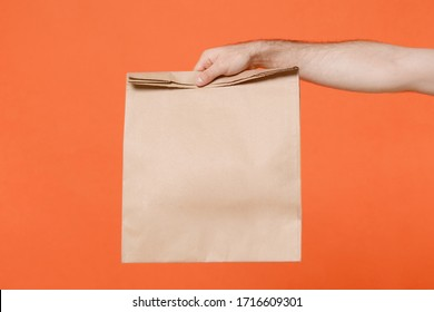 Close up cropped male hold brown empty blank paper bag for takeaway isolated on orange background. Food delivery service from restaurant shop to home. Epidemic pandemic coronavirus 2019-ncov covid-19