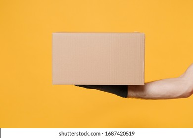 Close up cropped male hold in hand black glove brown clear blank paper empty cardboard box isolated on yellow background Packaging template mock up Delivery service concept Copyspace Advertising area