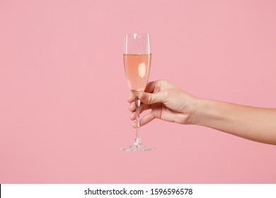 Close up cropped photo of female hold in hand glass of champagne isolated on pastel pink wall background. Copy space advertising mock up. Valentine's Day Women's Day birthday holiday party concept